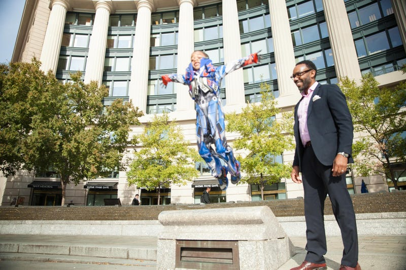"""Andre Perry and son Robeson at the U.S Navy Memorial in Washington, D.C. """"I need for Roby to fly around the world like a superhero,"""" says Perry.Gemal Wood, Park Triangle Productions"""