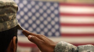 A soldier salutes the U.S. flag during a ceremony for troops returning home from Afghanistan on June 15, 2011, at Fort Carson, Colo.John Moore/Getty Images
