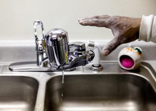 A handyman at the Shiloh Commonsin Flint, Mich., installs a new water filter in a residence Jan. 21, 2016.Sarah Rice/Getty Images