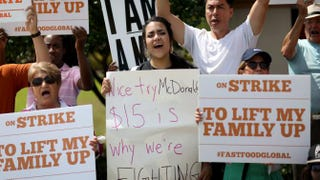 Protesters stand on the sidewalk outside a McDonald's restaurant in Miramar, Fla., April 2, 2015, asking that the chain raise its wages to $15 an hour.Joe Raedle/Getty Images