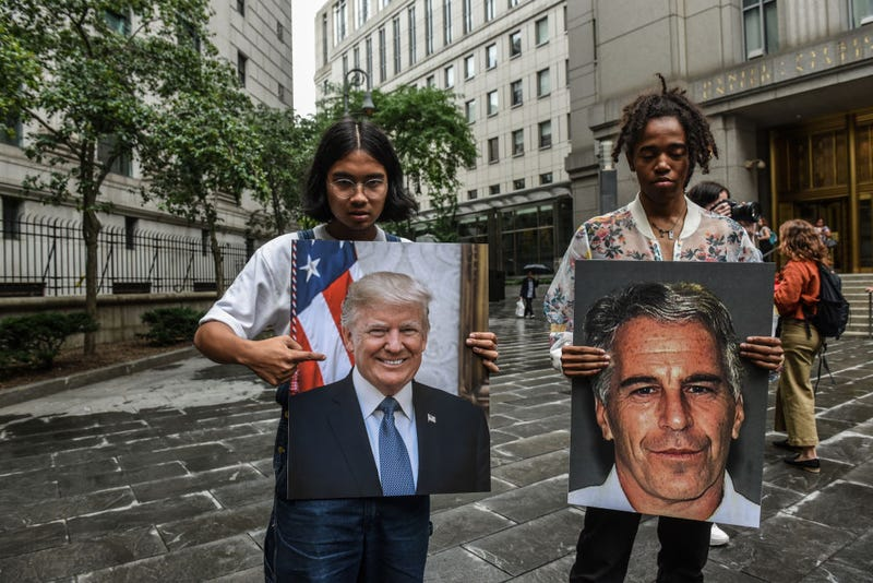 """A protest group called """"Hot Mess"""" hold up signs of Jeffrey Epstein and President Donald Trump in front of the Federal courthouse on July 8, 2019 in New York City."""