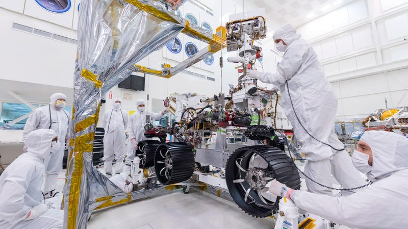 Jet Propulsion Lab engineers install three right-side wheels on the Mars 2020 rover.