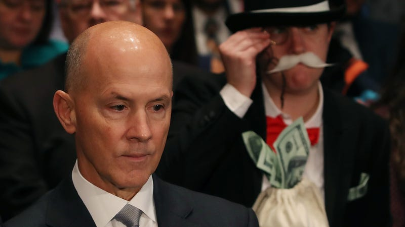 Former Equifax CEO Richard Smith flanked by a protester at a Senate hearing. Photo: Getty Images