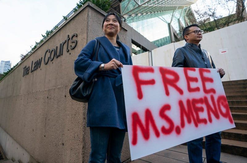 Supporters of Meng Wanzhou stand with a sign outside the British Columbia Supreme Court on December 10, 2018