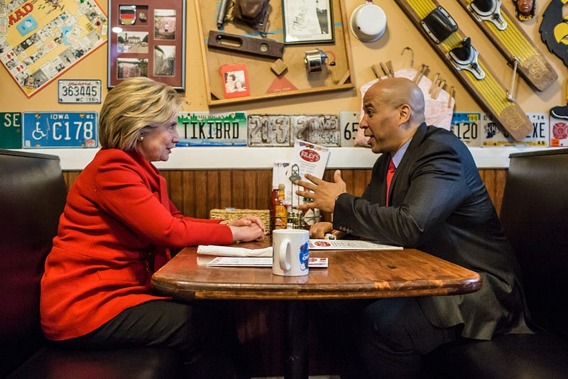 Democratic presidential candidate Hillary Clinton talks with Sen. Cory Booker (D-N.J.) at Riley's Cafe in Cedar Rapids, Iowa, on Jan. 24, 2016.Brendan Hoffman/Getty Images