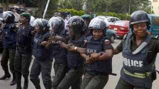 Police officers hold arms to block supporters of 219 schoolgirls kidnapped by Boko Haram militants from marching on the Nigerian president's official residence in Abuja on Oct. 14, 2014.Pius Utomi Ekpei/Getty Images