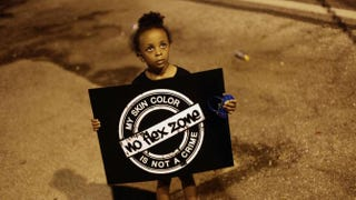 A girl holds a sign on Aug. 21, 2014, in Ferguson, Mo., as she protests the fatal shooting of Michael Brown by Ferguson Police Officer Darren Wilson on Aug. 9, 2014.Joshua LOTT/AFP/Getty Images