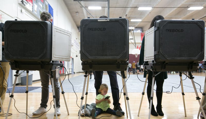 Sloane (no last name given), 2, waits between her father's legs as he and other voters cast their ballots at a polling station set up at Grady High School for the mid-term elections on November 6, 2018 in Atlanta, Georgia. Georgia has a tight race to elect the state's next Governor.