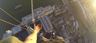 Illustration for article titled Guy jumps over huge gap to hang 490-feet above London with one hand