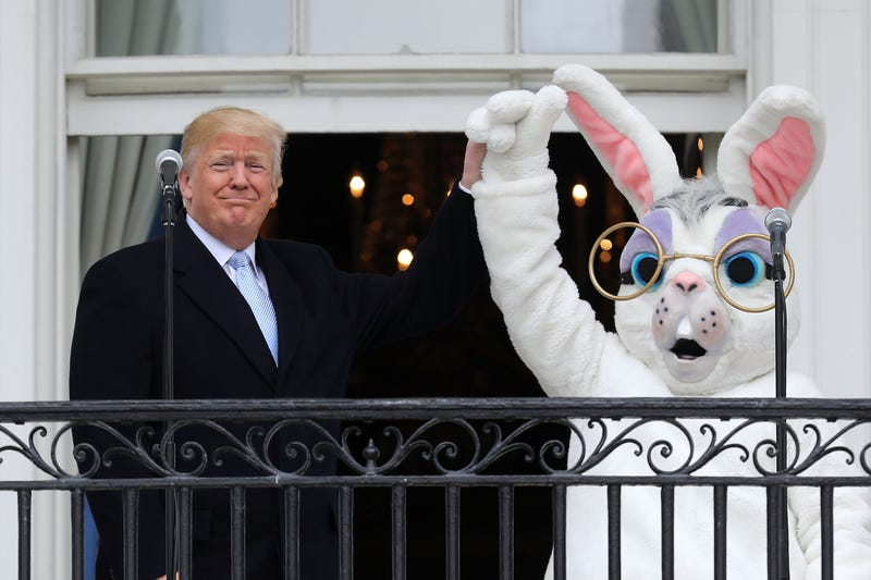 President Donald Trump lifts the Easter Bunny's hand on the Truman Balcony during the 140th annual Easter Egg Roll on the South Lawn of the White House on April 2, 2018, in Washington, D.C.