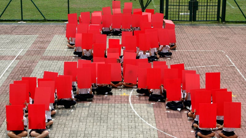About 100 students sit in the formation of the AIDS ribbon during an AIDS awareness program held in their school, Wednesday Aug. 16, 2006 in Singapore.