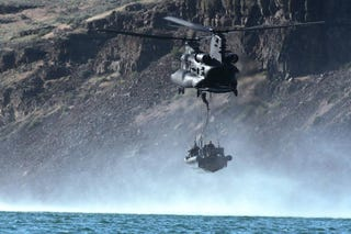 Illustration for article titled US Army helicopter drops an entire boat full of Navy Seals in the sea