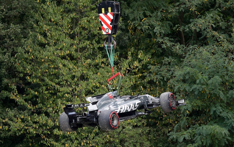 A crane removes Denmark driver Kevin Magnussen's Haas car from the the track during the second practice session for Sunday's Formula One Italian Grand Prix, at the Monza racetrack, Italy, Friday, Sept. 1, 2017. (AP Photo/Antonio Calanni)