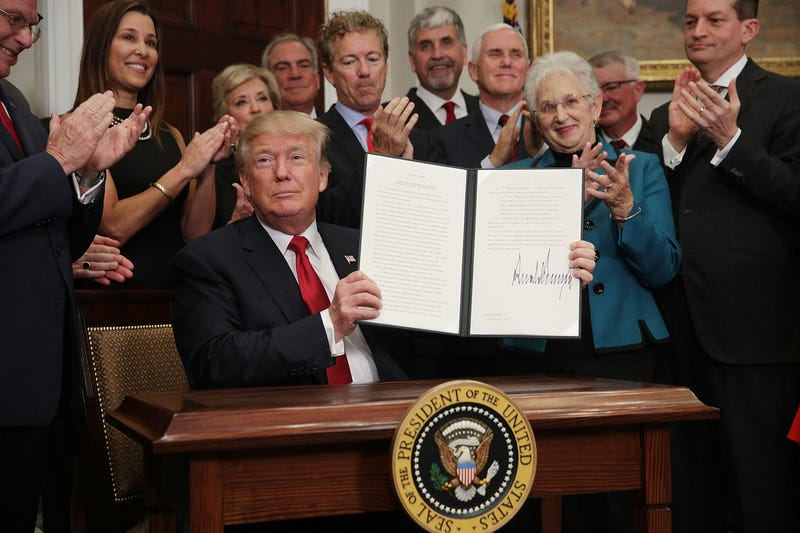 President Donald Trump shows an executive order to loosen restrictions on the Affordable Care Act on Oct. 12, 2017. (Alex Wong/Getty Images)