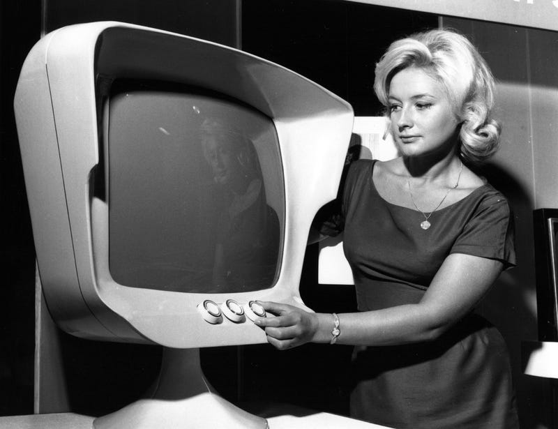 "Claire Collins examining the ""television of 1971,"" designed by John Denison-Hunt, at the 1961 Earls Court Radio Show (Getty Images)"