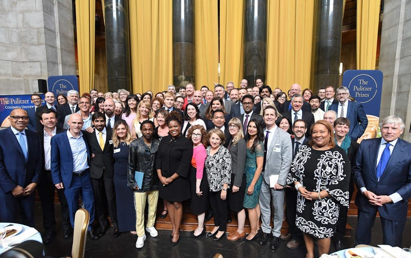 The 2018 Pulitzer Prize winners alongside Columbia University President Lee C. Bollinger and Pulitzer Board Chair Eugene Robinson. Pulitzer administrator Dana Canedy is pictured in a black-and-white dress near the far right.