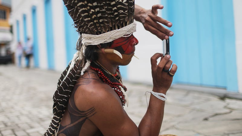 An indigenous tribe member takes a photo of another tribe member on a phone following a protest march for indigenous territorial rights on November 11, 2015 in Angra dos Reis, Brazil.