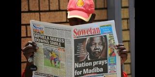 A man reads a newspaper bearing a photo offormer South African President Nelson Mandela. (Alexander Joe/AFP)