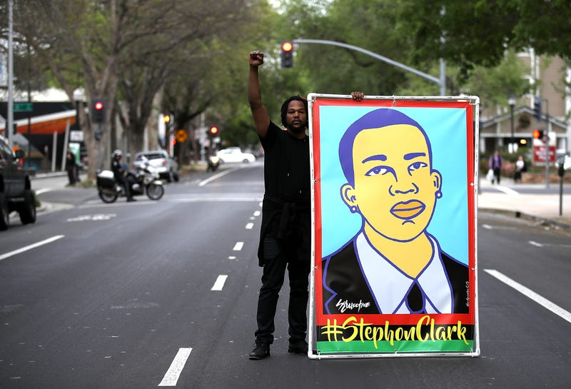A Black Lives Matter protester holds up an illustration of Stephon Clark during a march and demonstration through the streets of Sacramento, Calif., on April 4, 2018.