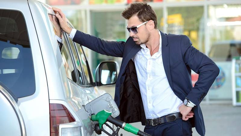A man in sunglasses is leaning against his car.