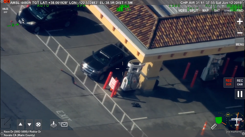 Police footage of a standoff resolved by a robot (seen below the pump closest to the pickup truck) that fulfilled the suspect's demand for a cigarette by delivering a vape pen.