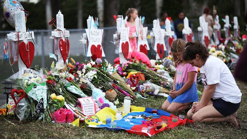 People visit a makeshift memorial setup in front of Marjory Stoneman Douglas High School in Parkland, Florida. (Photo: Getty)