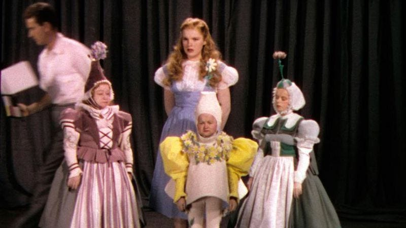 Hair and costume test for a blonde Judy Garland with three dispirited Munchkins,