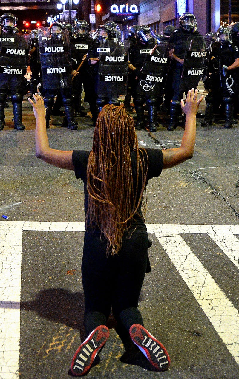 A protester places her arms in the air while on her knees in front of officers in riot gear at the intersection near the Epicentre in Charlotte, N.C., on Sept. 21, 2016.Jeff Siner/Charlotte Observer/TNS via Getty Images