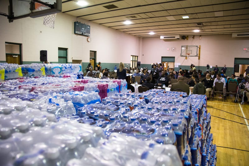 Bottled water can be seen on a gym floor in Flint, Mich., during a March 17, 2016, town hall meeting related to the lead-water crisis.