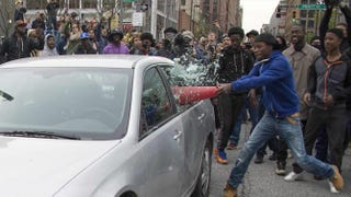 Demonstrator identified as Allen Bullockuses a traffic cone to break the window of a police car in Baltimore April 25, 2015, during protests of the death of Freddie Gray.JIM WATSON/AFP/GETTY IMAGES