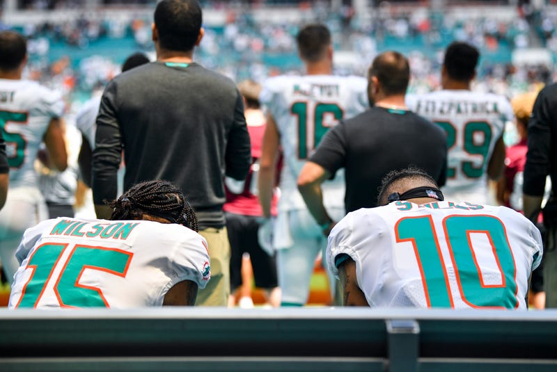 Albert Wilson #15 and Kenny Stills #10 of the Miami Dolphins sit during the National Anthem against the Tennessee Titans at Hard Rock Stadium on September 9, 2018 in Miami, Florida.