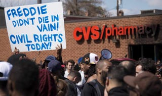 Demonstrators hold up a placard near the CVS Pharmacy on Pennsylvania Avenue in Baltimore that was looted and burned April 28, 2015.JIM WATSON/AFP/Getty Images
