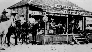 """A horse thief is tried in court in 1900. The thief is sitting on a horse underneath the """"Ice Beer"""" sign, with his hands behind his back.National Archives and Records Administration"""