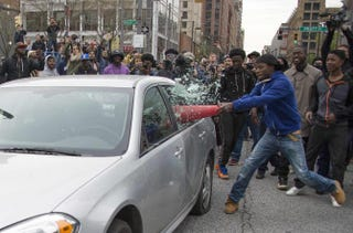 Demonstrator identified as Allen Bullock uses a traffic cone to break the window of a police car in Baltimore April 25, 2015, during protests of the death of Freddie Gray.JIM WATSON/AFP/Getty Images