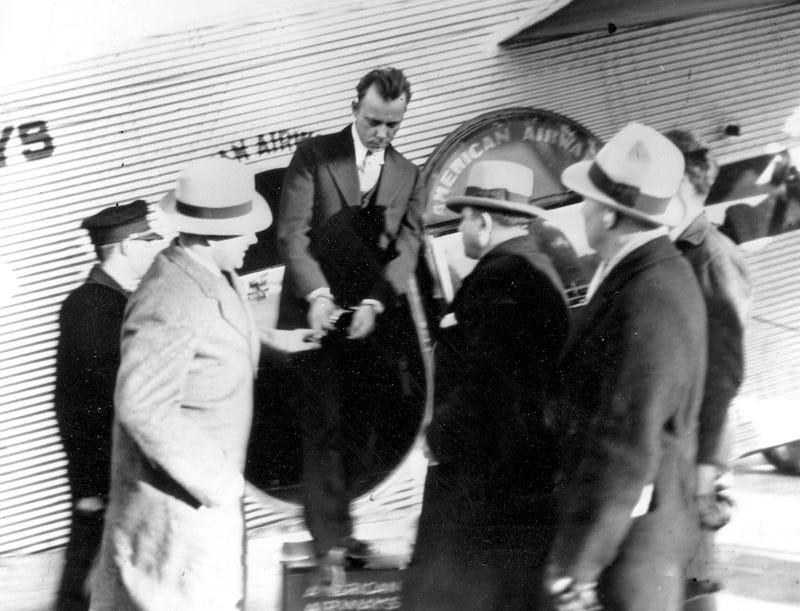 John Dillinger is shown on January 30, 1934, as he's taken from one plane to another in St. Louis, Tennessee on his way to an Indiana jail