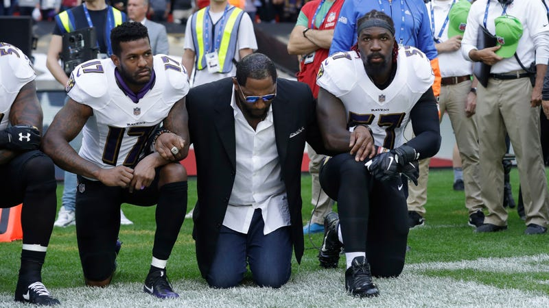 Ray Lewis (center) kneels between two Baltimore Ravens players during the playing of the national anthem before a game. (Matt Dunham/AP Images)