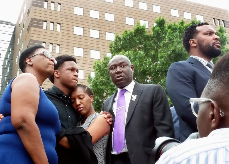 Allison Jean, left, the mother of Botham Jean, stands with Botham's brother Brandt, second from left, and sister, Allisa Charles-Findley, along with attorneys Benjamin Crump, second from right, and Lee Merritt, right, during a news conference Monday, Sept. 10, 2018