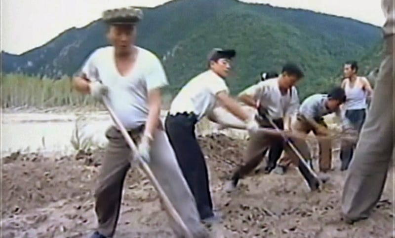 North Korean workers build levees along a river bank in an undated image from a video released by state media on Monday. Image: KRT via AP