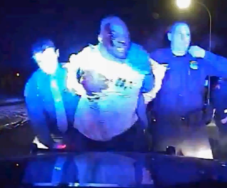 Dash-cam video screenshot showing a bloodied Floyd Dent being held up by officers.Detroit Free Press