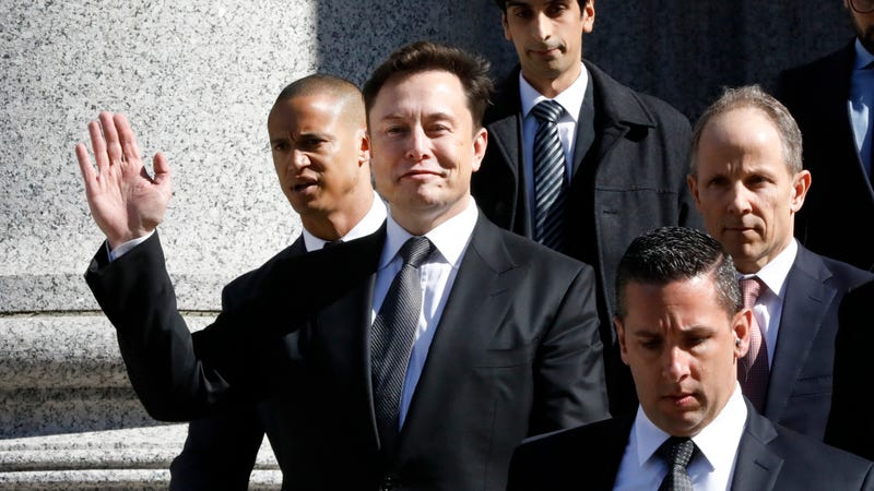 Tesla boss Elon Musk beckons as he leaves Manhattan Federal Court on Thursday, April 4, 2019.