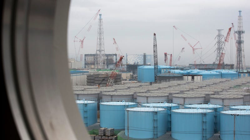 Storage tanks for contaminated water are seen through a window of a building during a media tour to the tsunami-damaged Fukushima nuclear power plant. (Image: AP)