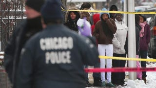 Neighborhood residents watch as police investigate a homicide scene after a 24-year-old man was found dead with a gunshot to his back in the Lawndale neighborhood on December 15, 2013 in ChicagoScott Olson/Getty Images