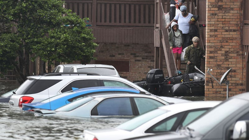 People are led down a staircase to a rescue boat after the flooding of Hurricane Harvey inundated their apartment complex on August 30, 2017 in Port Arthur, Texas. Image via Getty.