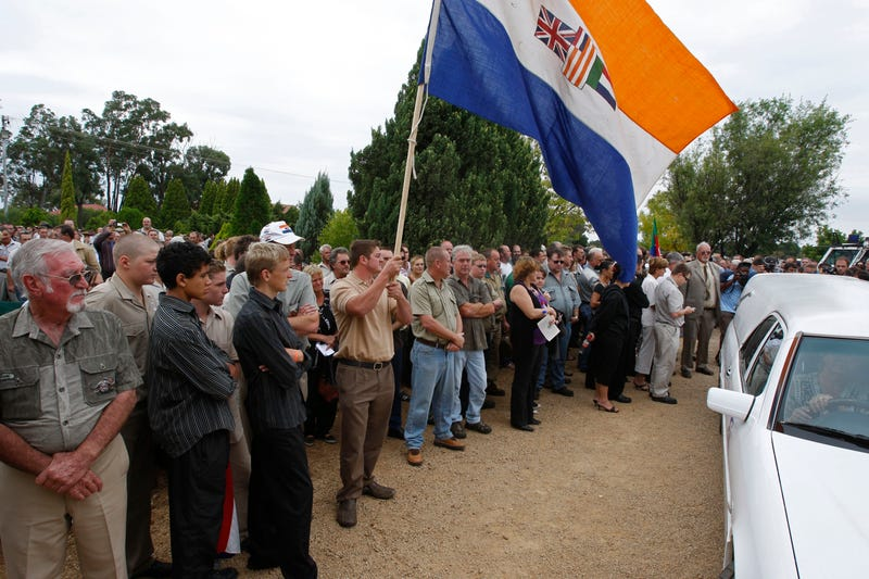 Supporters, hold a former South African apartheid government flag as slain white supremacist leader Eugene Terreblanche, coffin arrives at the church in Ventersdorp, South Africa, Friday, April 9, 2010.
