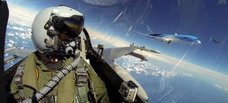 Illustration for article titled Extremely rare photo of two armed F-16s escorting a Boeing Dreamliner
