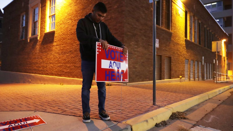 Volunteer Albert Lopez, 18, puts up a Spanish-language voting sign in El Paso, Texas, a predominantly Latinx border town that voted blue this year.