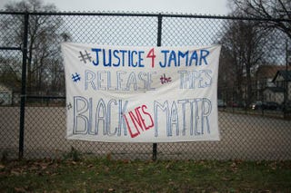 A sign demanding the release of video footage of the killing of Jamar Clark hangs on a fence during a candlelight vigil held for Clark outside the 4th Police Precinct in Minneapolis Nov. 20, 2015.Stephen Maturen/Getty Images