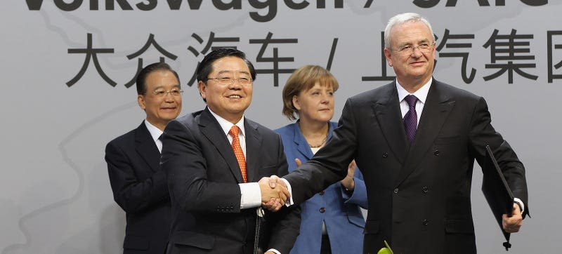 Xu Jianyi shakes hands with now-stepped-down VW boss Martin Winterkorn in 2012. Photo Credit: Getty Images