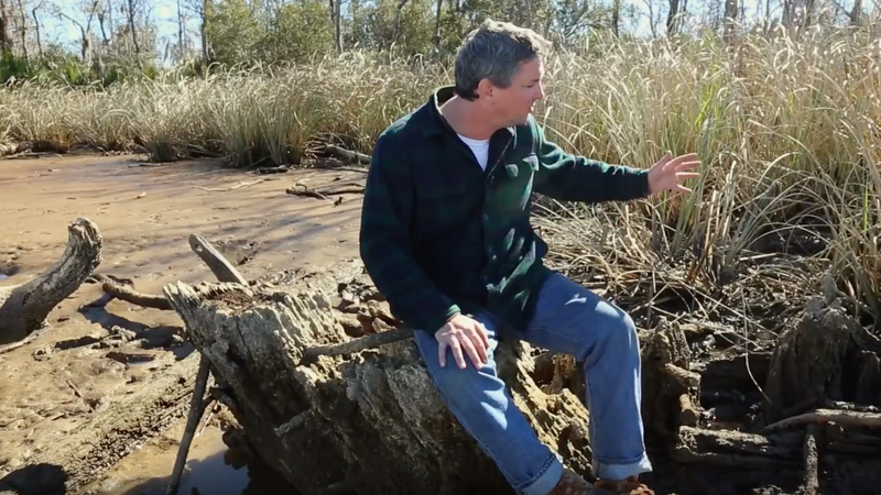 AL.com reporter Ben Raines sits among the wreckage that archeologists believe may be the remnants of the Clotilda. (AL.com via YouTube screenshot)