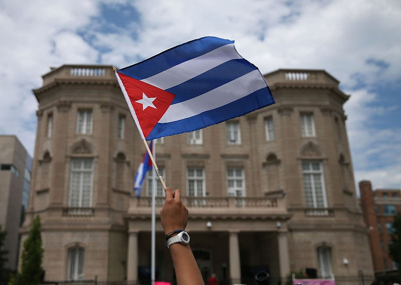 A supporter waves a Cuban flag in front of the country's embassy after it reopened for the first time in 54 years July 20, 2015, in Washington, D.C.Mark Wilson/Getty Images